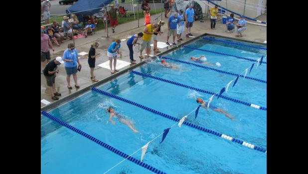Swimmers make their way to the finish line in a heat of the 25-meter backstroke event last Saturday during an invitational meet hosted by the Anna Blue Dolphins swim team. The meet was at the Anna City Pool in Anna.
