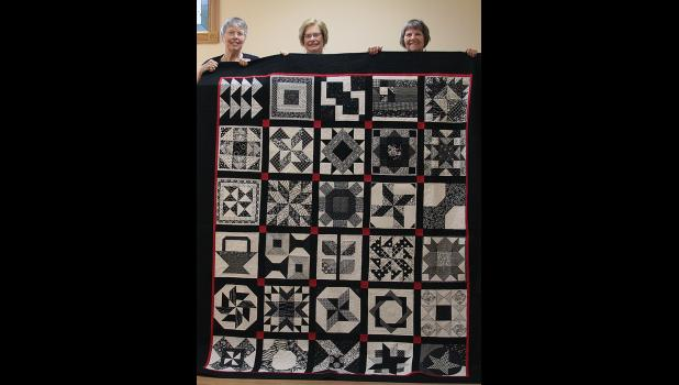 Common Threads Quilt Guild members Donna Budelsky, Elaine Dunn and Susan Askew display this year's quilt for the American Cancer Society raffle. Photo provided.