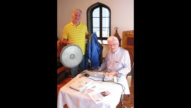 Former WRAJ radio employee Tim Jones, left, presented a special memento to Don Michel. Jones gave Michel a turntable which had been used when WRAJ was in operation in Anna.