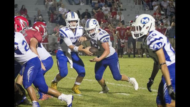Anna-Jonesboro quarterback Bryce Osman, number 14 and a senior, hands the ball to senior Jayce Turner, number 42, in Friday night's game at West Frankfort. Also in the photo are junior Damien Chrisp, number 27, and junior Nate Kissat, number 20. Photo by Tiffiny Dillow for The Gazette-Democrat.