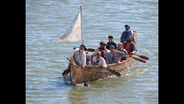 A voyageurs canoe is paddled to shore along the Ohio River by a crew of reenactors. Fort Massac State Park, home of the annual encampment, overlooks the Ohio River.
