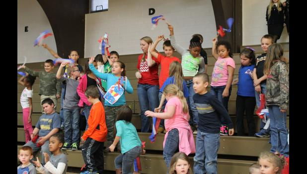 As veterans were recognized, elementary students cheered and waved hand-made patriotic flags.