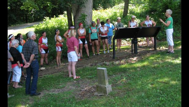 Sandra  Boaz, standing at right, shared information about the history of the Camp Ground Church area last Sunday afternoon with participants in the 2018 Remember the Removal Bike Ride.
