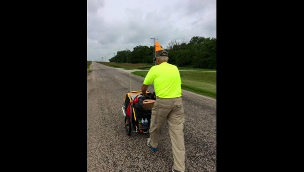 85-year-old Dean Troutman pushed the same buggy for 700 miles in 2015 to raise funds to build a park in honor of his wife.