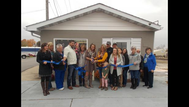 Surrounded by friends and family, new business owners Betsy Oxford and Kassi Needling cut the ribbon at the grand opening of their new businesses. Photo by Benjamin Marxer.
