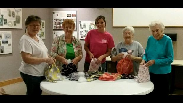 From left are Sue Johnson, June Badgley, guest Jessica Wright, Anna Doardi and Alice Mae Mathis, who filled the underarm hanging pillows with fiberfill in order to provide a comfortable cushion for hospital patients who are recovering from breast surgery. Photo provided.