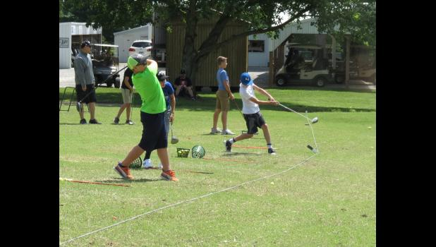 Instructor Davin Hannuksela helped on the driving range during the junior golf program.