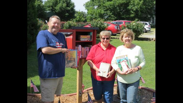 From left are Lyle and Tammy Woodrum, owners of The Davie School Inn & Suites in Anna, and Alice Kerns, secretary of the Friends of Stinson Library Board. They are holding books for a new Little Free Library which is located on the grounds of the Anna bed and breakfast business.