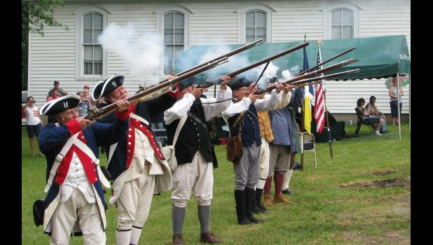 Members of an Illinois Society Sons of the American Revolution color guard  fired a musket salute during the ceremony.