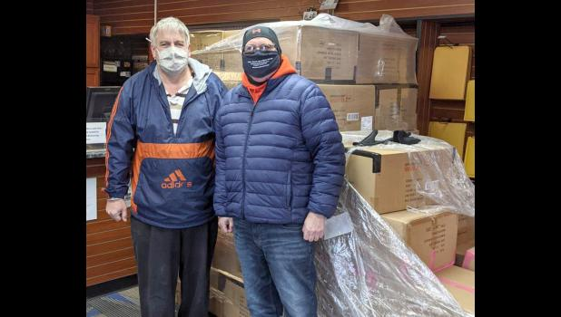 Each year Postal Pal in Anna covers the cost of shipping the coats for the campaign, which allows for 100 percent of all donations to be used to buy the coats. From left are Kevin Hess of Postal Pal and Moury Bass of WIBH. Photo provided.
