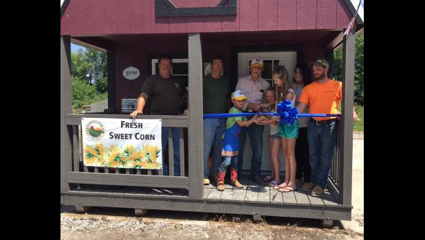 "Henry and Carley Pearson wielded novelty scissors to cut the ribbon and declare Pearson Farms new roadside produce store officially open. The Pearson family includes, from left to right, Richie Pearson, Wayne Pearson, Henry ""Strawboss"" Pearson, Kenneth Pearson, Carley Pearson, Mackenzie Pearson, Jessie Pearson and Matt ""Sparkplug"" Pearson."
