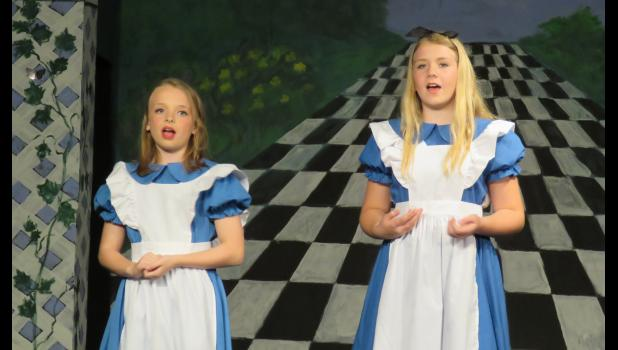 Brinley Corbit, left, as Alice Through the Looking Glass, and Jossilin Needling, as Alice in Wonderland, set the scene for the audience.