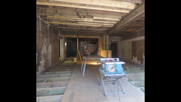The flooring and portions of the wall needed to be replaced in the former Union County Pharmacy building before it could become The Gathering Place. Store manager Susan Whitemountain plans to offer genealogy and researching services to the community. Photo by Amber Skelton.