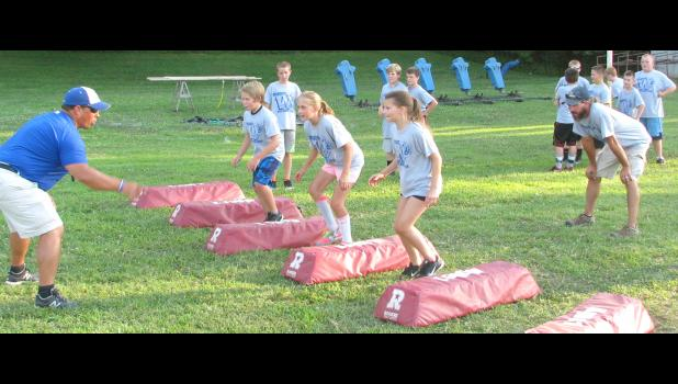 Youth football league campers, including Clohie Powell of Anna and Megan Wright of Anna, took part in a drill led by Brett Detering. Detering is head football coach at Anna-Jonesboro Community High School.